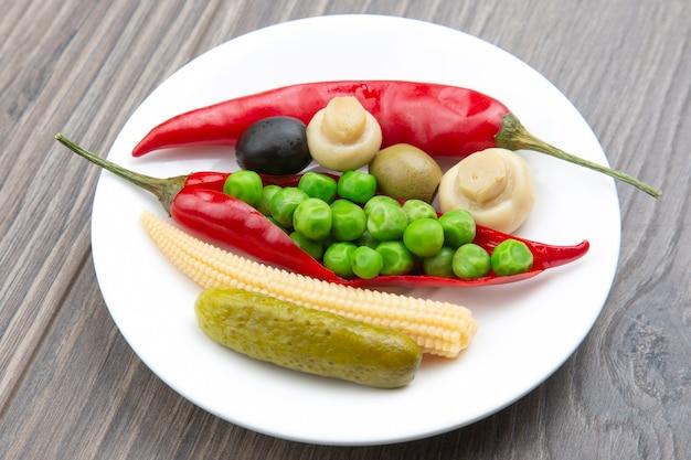 Oliven, eingelegte gurken, pfeffer, pilze und mais in einem salat auf einem teller. essen und gemüse. diät und gewichtsverlust