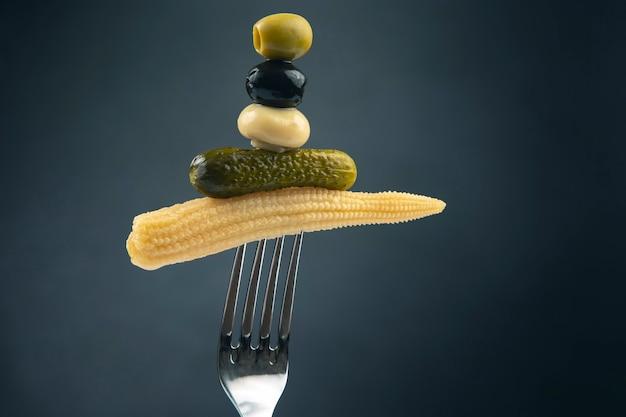 Oliven, eingelegte gurken, pilze und mais auf einer gabel nahaufnahme auf einer dunkelheit. essen und gemüse
