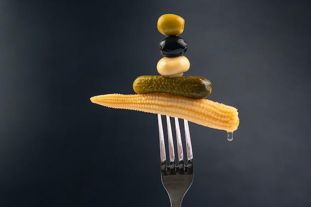 Oliven, eingelegte gurken, pilze und mais auf einer gabel nahaufnahme. essen und gemüse