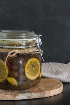 Oliven in einem glas in öl mit zitronenscheiben auf dunklem hintergrund.