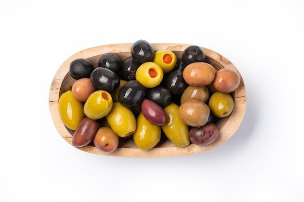 Oliven in einer holzschale vor einem weißen hintergrund isoliert, mit beschneidungspfad