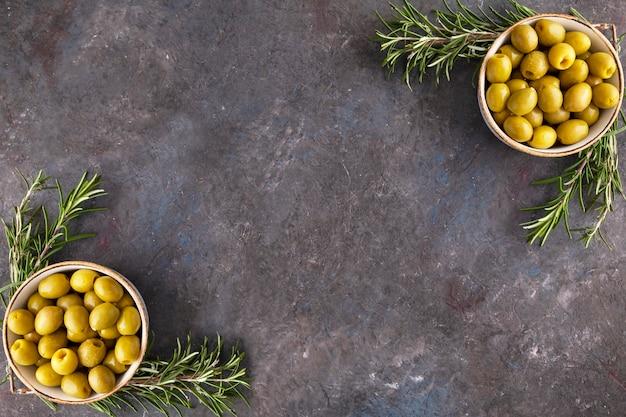 Oliven in einer schüssel und rosmarin mit platz zum kopieren. draufsicht