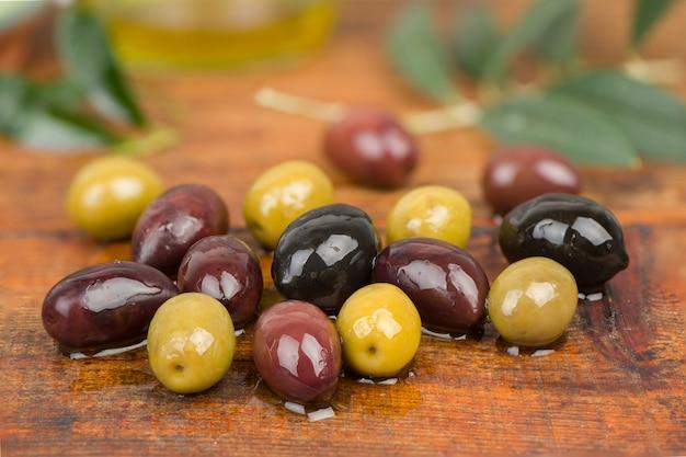 Oliven in öl auf holztisch.