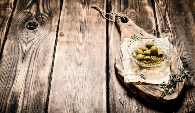 Oliven in öl- und rosmarinzweigen an der tafel.