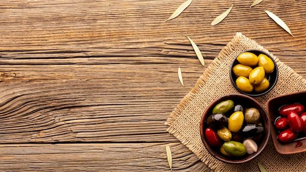 Oliven in schüsseln auf textilmaterial mit kopienraum