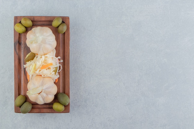 Oliven-knoblauch-sauerkraut-salat auf der holzplatte auf der marmoroberfläche
