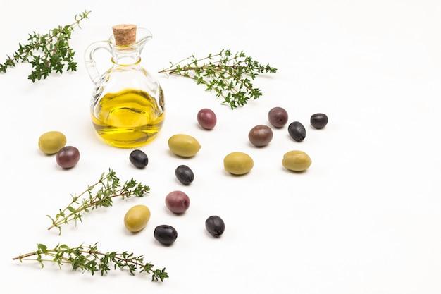Oliven liegen auf dem tisch. thymianzweige. olivenölflasche. draufsicht