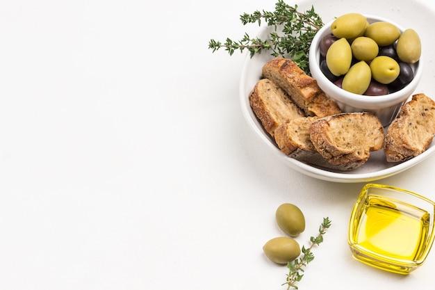 Oliven und brotscheiben in keramikschale. draufsicht