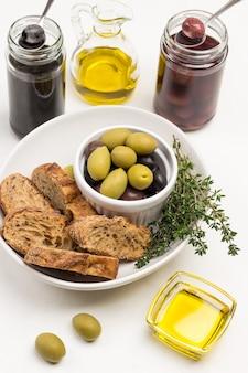 Oliven und brotscheiben in keramikschale. oliven und olivenöl in gläsern. draufsicht