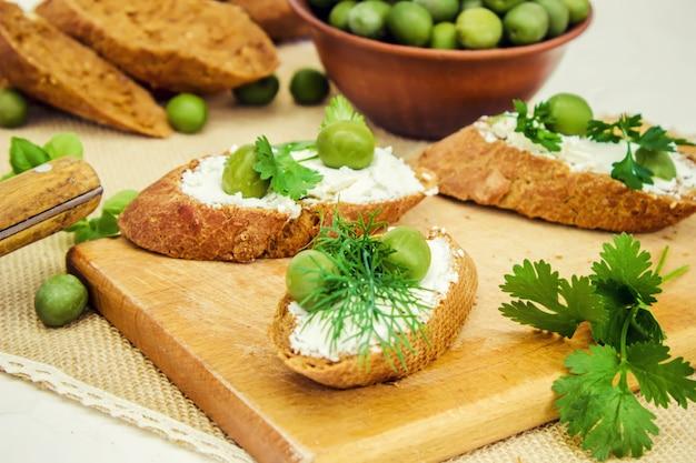 Oliven und käse auf einem weißen hintergrund. sandwiches. selektiver fokus.