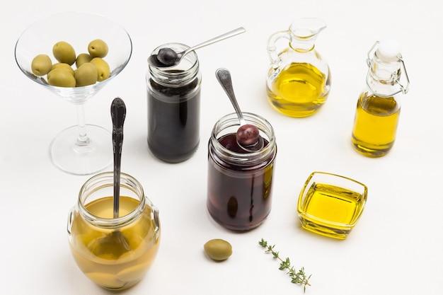 Oliven und olivenöl in gläsern. draufsicht