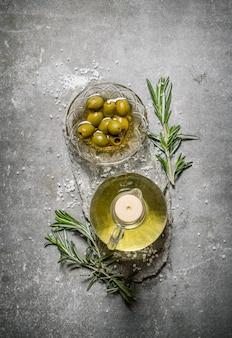 Oliven und olivenöl mit rosmarinzweigen.