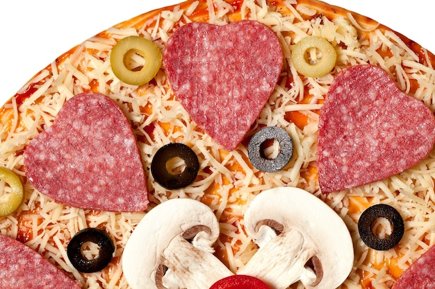 Oliven, wurst, pilze und käse liegen auf dem pizzateig