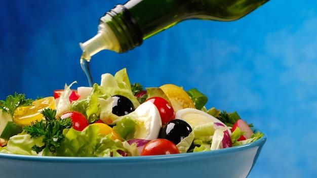 Olivenöl, das von der flasche auf gemüsesalat, gesundes und diätetisches essen von frischen bestandteilen in der schüssel auf blauem hintergrund gießt