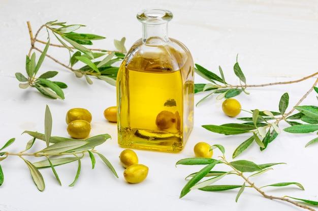 Olivenöl extra vergine in glasflasche. vordergrund. beinhaltet blätter und olivenzweige.