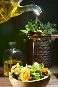 Olivenöl fällt auf zwei oliven mit olivenblättern, um einen mediterranen salat zu würzen.