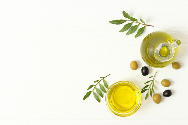 Olivenöl grüne blätter und oliven auf dem tisch