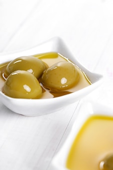 Olivenöl in der schüssel mit oliven