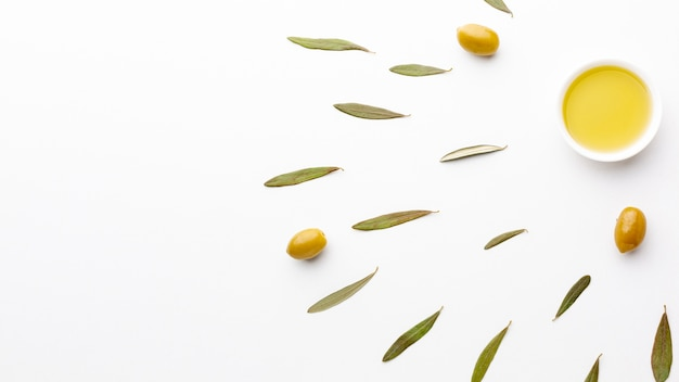 Olivenöl in der untertasse mit blättern und kopienraum
