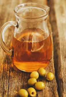 Olivenöl in einem glas mit oliven