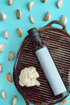 Olivenöl in einer flasche auf einem grill mit knoblauch und brokkoli. pastellblau