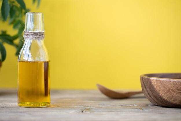 Olivenöl in einer flasche, einem löffel, einem teller und einer blume in einem topf auf einem holztisch auf gelbem grund. platz kopieren.