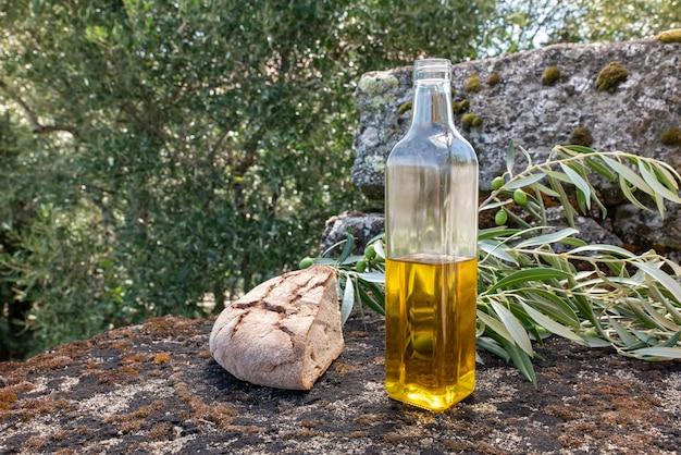 Olivenöl in einer flasche in der natur mit einem olivenzweig und einem felsigen boden