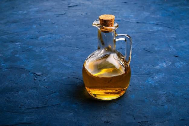Olivenöl in glasflasche auf blauem tisch Premium Fotos
