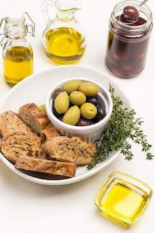 Olivenöl in glasschüssel. oliven, brot und thymian in keramikschale. olivenölflaschen. oliven im glas. draufsicht