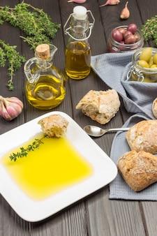 Olivenöl in weißer platte mit brotscheibe und thymianzweig. brotstücke und oliven im glas auf grauer serviette. olivenöl in der flasche, thymianzweige. draufsicht