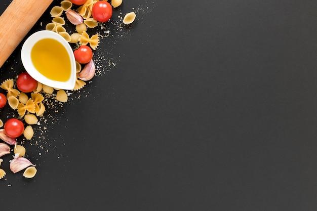 Olivenöl; kirschtomate mit rohen italienischen teigwaren über schwarzem hintergrund