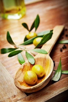 Olivenöl mit frischen oliven auf rustikalem holz