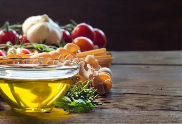 Olivenöl, nudeln, knoblauch und tomaten auf braunem holztisch schließen mit kopienraum