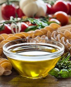 Olivenöl, nudeln, knoblauch und tomaten auf braunem holztisch schließen oben