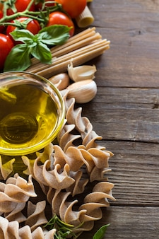 Olivenöl, nudeln, knoblauch und tomaten auf dem holztisch schließen oben