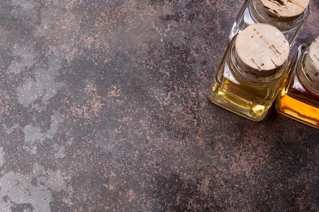 Olivenöl- und essigflaschen auf rustikalem hintergrund mit kopierraum