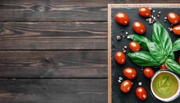 Olivenöl und kirschtomaten mit basilikumblättern, salz und pfeffer, layout auf einem schwarzen steinbrett. zutaten für die herstellung von caprese-salat. kopieren sie raum auf einem dunklen hölzernen hintergrund, draufsicht