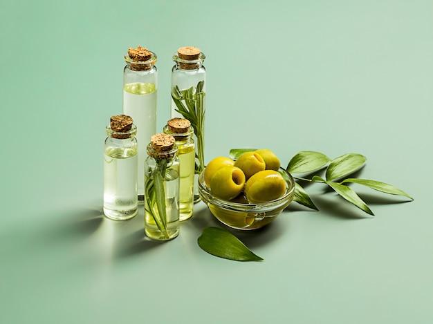 Olivenöl und olivenzweig auf dem holztisch