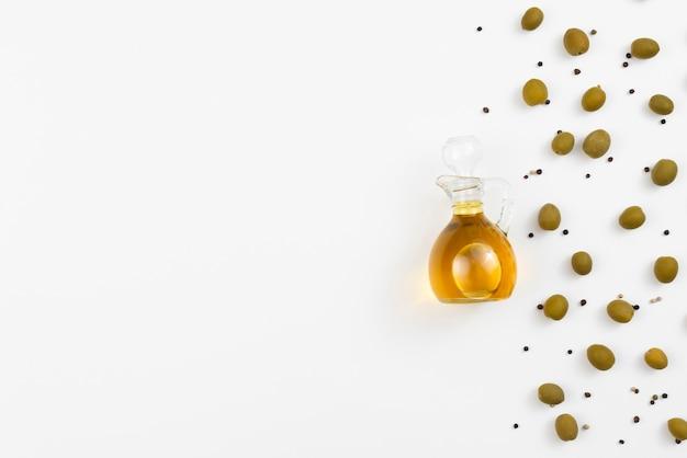 Olivenölflasche mit oliven als nächstes