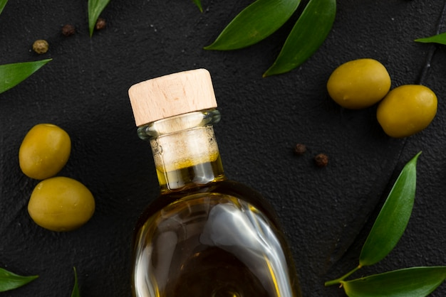 Olivenölflasche mit oliven und blättern als nächstes