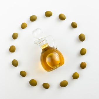 Olivenölflasche umgeben durch grüne oliven