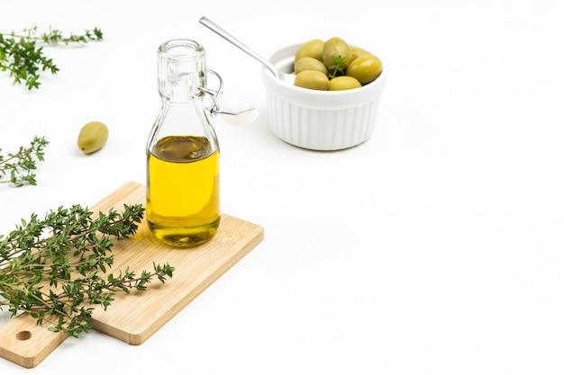 Olivenölflasche und thymianzweige an bord. oliven in keramikschale. draufsicht.