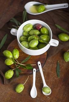 Olivenzweig auf der schwarzen holzoberfläche