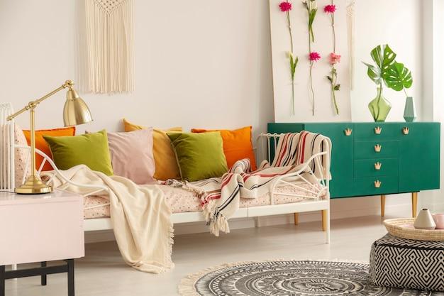 Olivgrüne, pastellrosa, gelbe und orangefarbene kissen auf einem einzelnen metallbett mit gemusterter bettwäsche im boho-schlafzimmer-interieur für mädchen