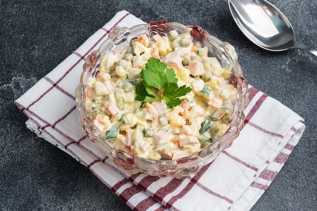 Oliviersalat mit mayonnaise auf einem teller. russisch ist ein traditionelles festliches gericht.