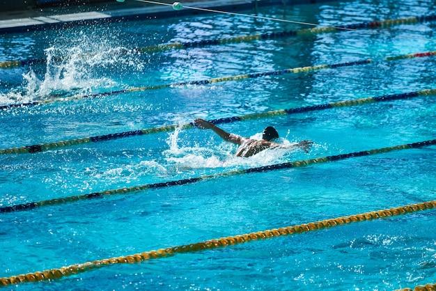 Olympisches sportbecken mit nicht erkennbaren menschen, die im wasser schwimmen.