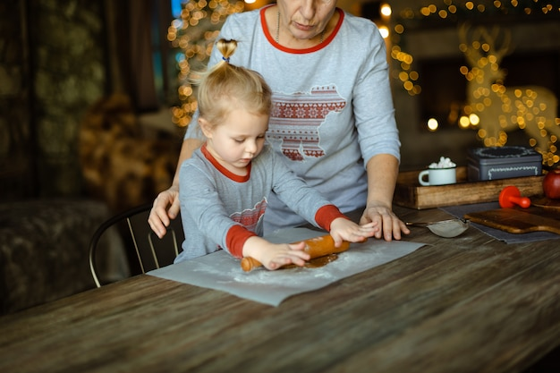 Oma hilft ihrer enkelin, den teig für einen traditionellen weihnachts-ingwer-keks auszurollen