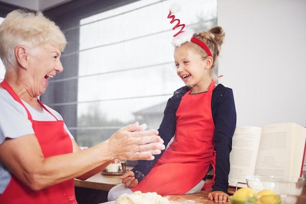 Oma mit mädchen, das in der küche genießt