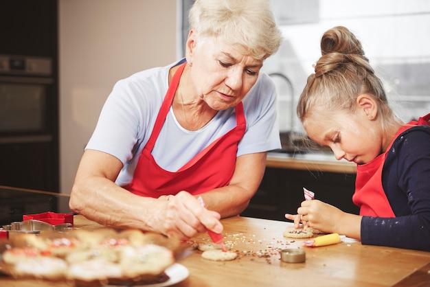 Oma mit mädchen, das zusammen kekse backt und verziert