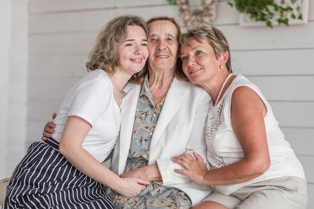 Oma; mutter und tochter umarmen sich und lächeln, während sie zu hause auf der couch sitzen